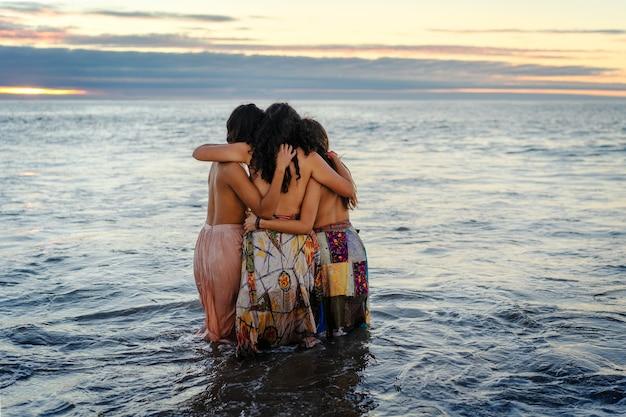 Tre giovani donne latine si abbracciano nell'acqua al tramonto mostrando amicizia o sorellanza