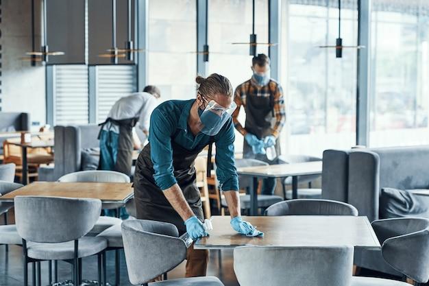 Tre giovani camerieri in tavoli protettivi per la pulizia di indumenti da lavoro per i clienti del ristorante clients