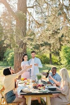 Tre giovani coppie multiculturali tintinnano con bicchieri di vino sul tavolo festivo servito mentre si gusta una cena all'aperto sotto l'albero di pino