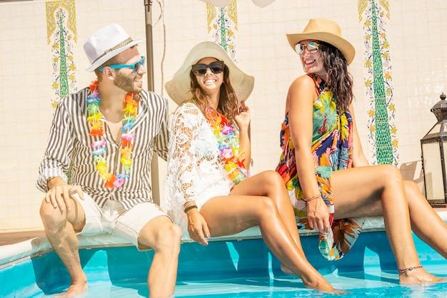 Tre giovani seduti sul bordo di una piscina sorridenti