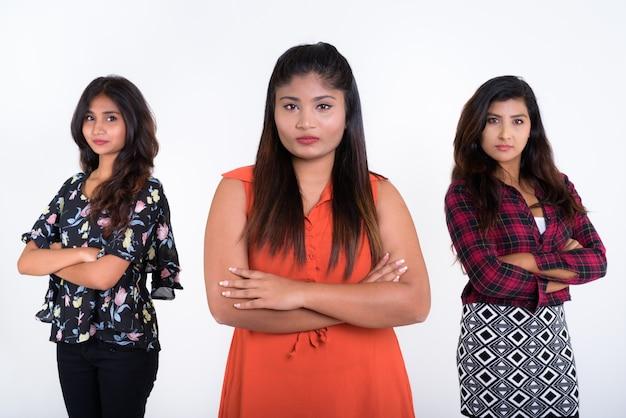 Tre giovani amiche persiane con le braccia incrociate insieme