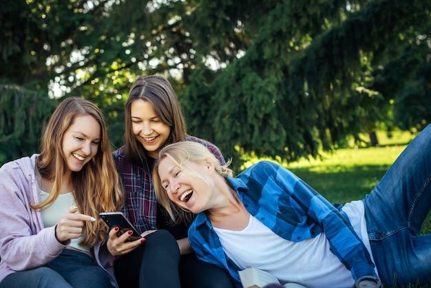 Tre giovani donne graziose sul prato nel parco guardano smartphone e ridono. le studentesse si rilassano nel parco che si siede sull'erba verde.