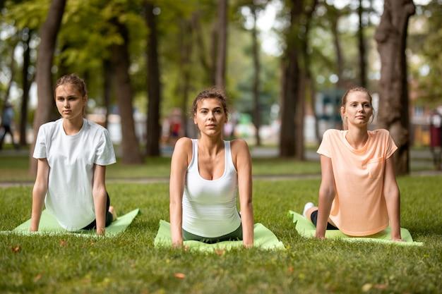 Tre giovani ragazze snelle che fanno stretching su stuoie di yoga sull'erba verde nel parco in una giornata calda. yoga all'aria aperta.