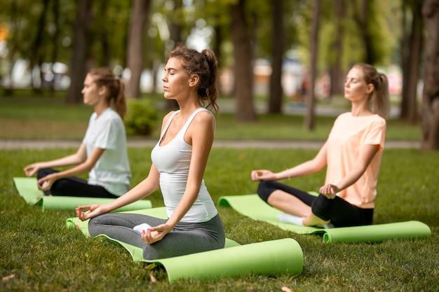 Tre giovani ragazze magre si siedono nelle posizioni del loto con gli occhi chiusi facendo yoga su stuoie di yoga sull'erba verde nel parco in una giornata calda.