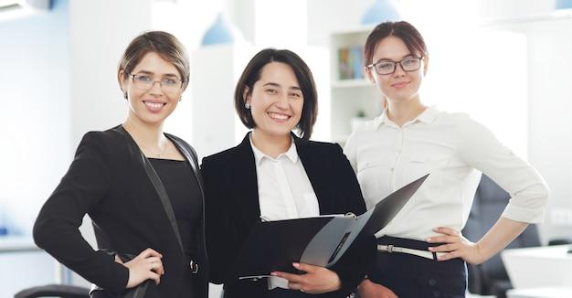 Tre giovani donne d'affari di successo in ufficio sorridendo felicemente.