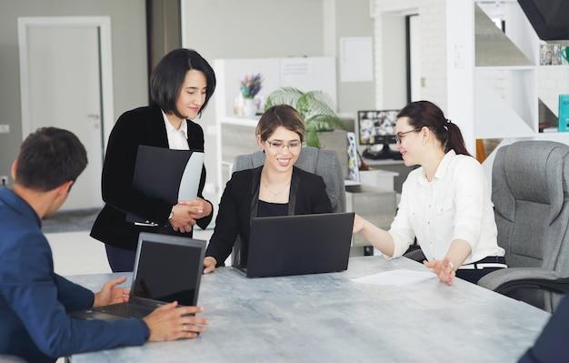 Tre giovani donne d'affari di successo in ufficio lavorano insieme felicemente a un progetto