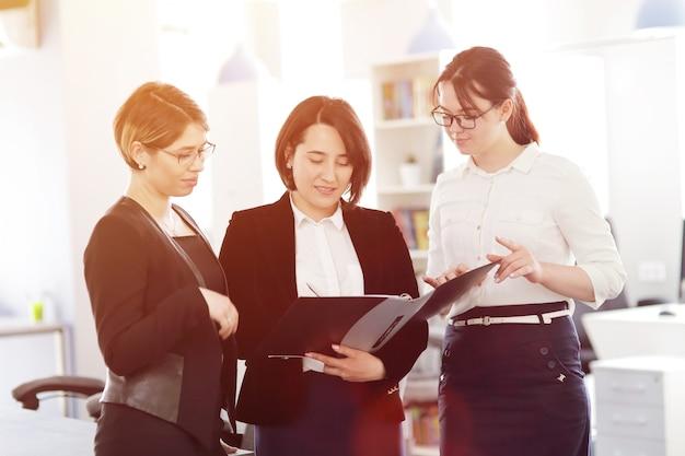 Tre giovani donne d'affari di successo in ufficio che lavorano insieme su un progetto.