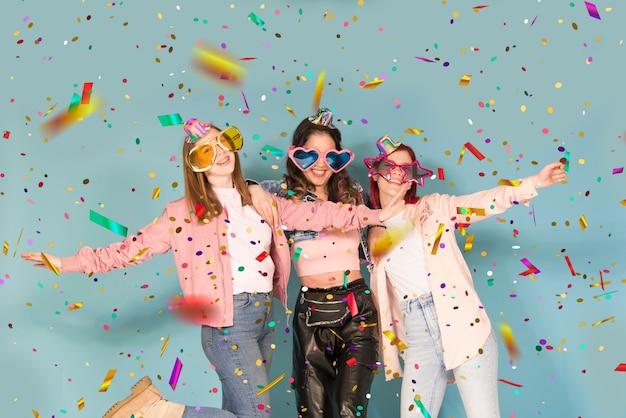 Tre giovani ragazze adolescenti che fanno festa con i coriandoli
