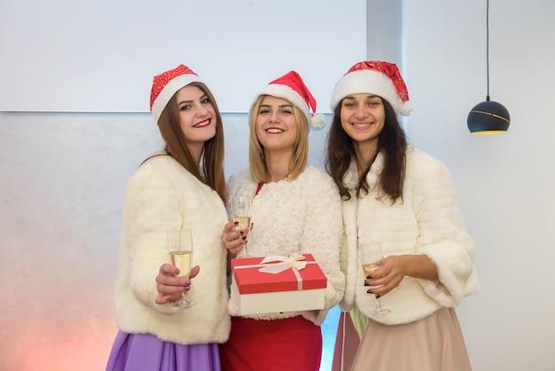 Tre giovani donne con cappelli di babbo natale con scatola regalo e bicchieri di champagne