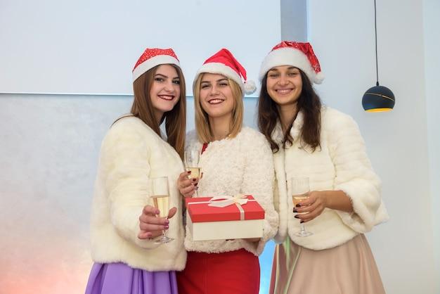 Tre giovani donne in cappelli di babbo natale con confezione regalo e bicchieri di champagne