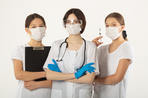 Tre giovani donne in abiti medici su uno sfondo bianco
