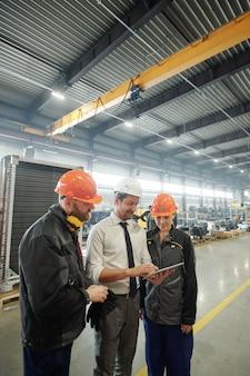 Tre giovani operai dell'impianto industriale discutendo disegno tecnico del dettaglio della macchina alla riunione in officina