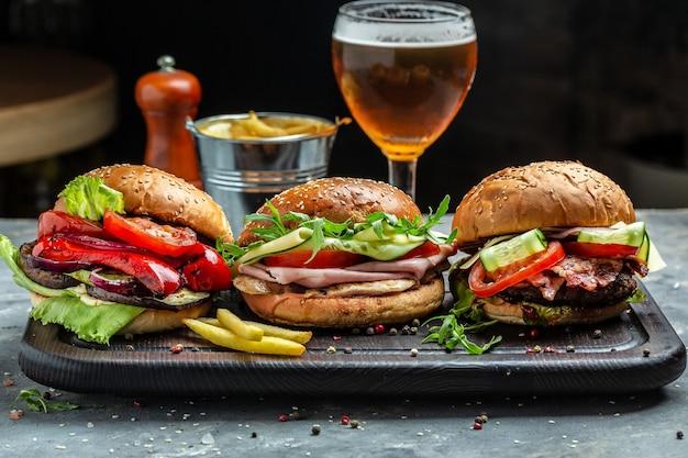 Tre deliziosi hamburger succosi con doppia cotoletta e formaggio. hamburger di carne alla griglia con birra. grande hamburger, fast food americano. banner, menu, posto ricetta per il testo