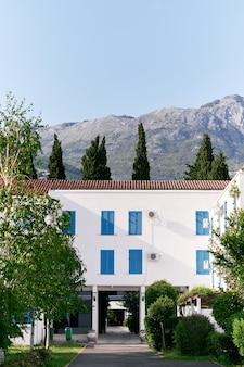 Casa bianca a tre piani immersa nel verde sullo sfondo delle montagne