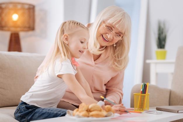 Attraverso generazioni. felice donna invecchiata positiva con gli occhiali e guardando i suoi nipoti disegnare mentre trascorreva del tempo insieme a lei
