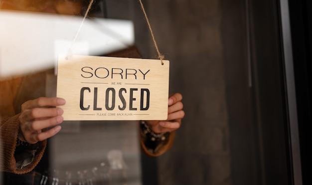 Attraverso la vista in vetro della donna imprenditrice che appende il cartello con l'iscrizione chiusa alla fine