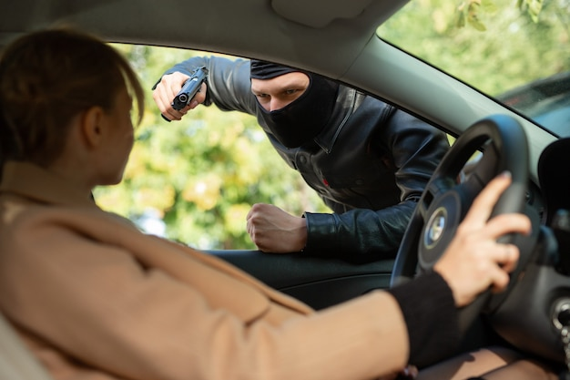 Delinquente in maschera nera minaccia una donna con una pistola mentre guida un'auto