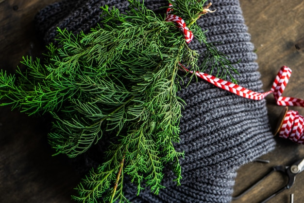 Pianta sempreverde thuja in bouquet con nastro rosso e bianco su sfondo sciarpa lavorata a maglia