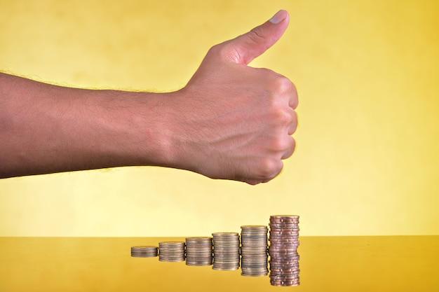 Segno di pollice in su sulla pila di monete