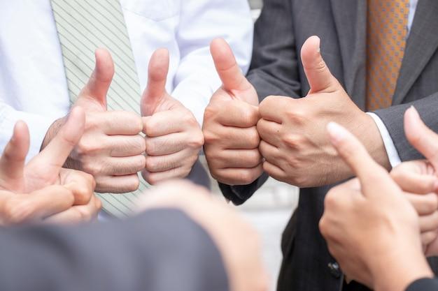 Pollice su lavoro di squadra di uomini d'affari