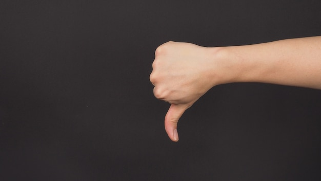 Il pollice verso il segno della mano su sfondo nero. si usa quando non ti piace o approvi qualcosa.