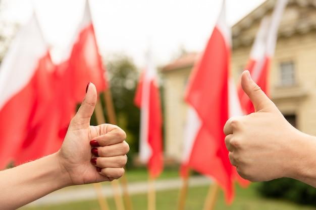 Pollice in alto gesto con le bandiere della polonia dietro