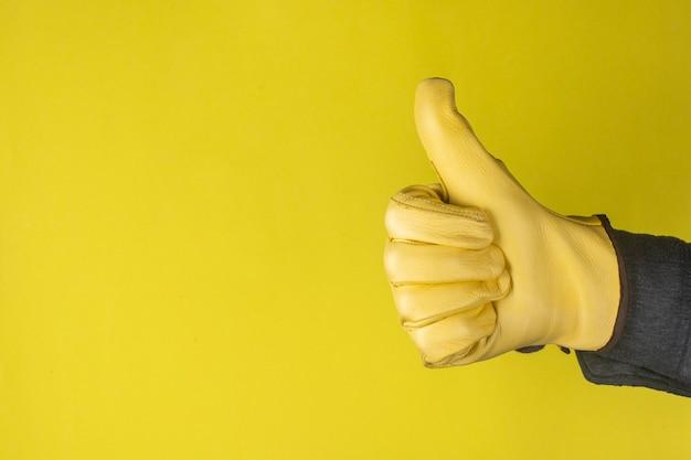 Thumbs up mano guantata su uno sfondo giallo