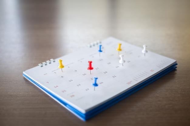 Puntina da disegno nel concetto di calendario per promemoria di impegni, appuntamenti e riunioni.