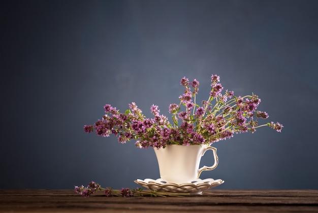 Fiori di timo in tazza vintage bianca sulla tavola di legno su sfondo blu