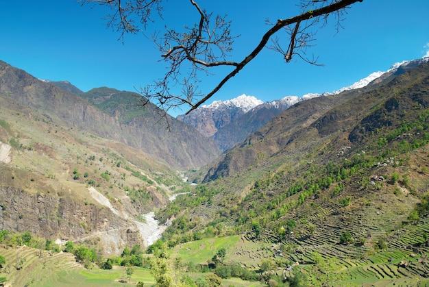 Paesaggio della montagna tibetana con cielo, campo e verde vallata