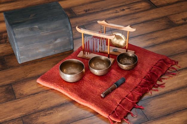 Campane tibetane sul pavimento nella lezione di yoga, concetto di terapia del suono