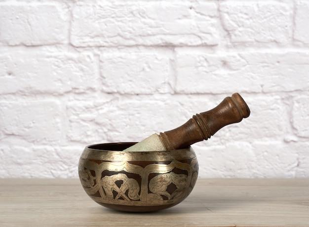 Ciotola di rame di canto tibetano con un batacchio di legno sulla tavola di legno marrone