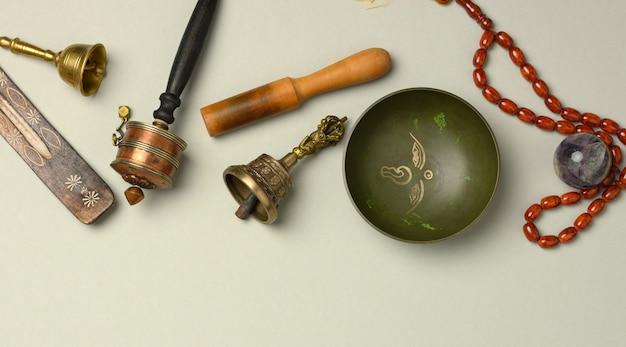 Canto tibetano ciotola di rame con un batacchio di legno su uno sfondo grigio, oggetti per la meditazione e la medicina alternativa, vista dall'alto