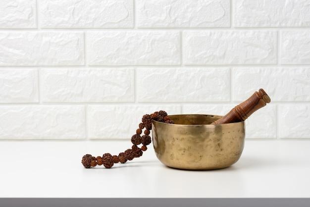 Canto tibetano ciotola di rame con un batacchio di legno su un tavolo di legno bianco, oggetti per la meditazione e la medicina alternativa