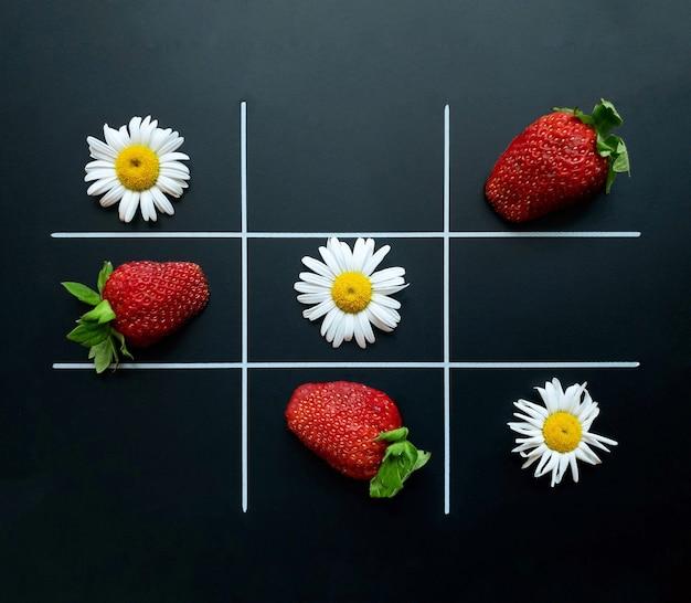 Tic tac toe su uno sfondo nero fatto di fiori di camomilla e fragole. disposizione piatta. concetto naturale.