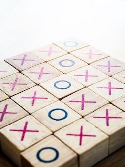Tic tac toe, tabellone di gioco del bue realizzato da un blocco di legno isolato su sfondo bianco, stile verticale.