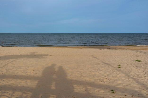 Flusso di acqua di marea sulla spiaggia e cielo blu in estate.