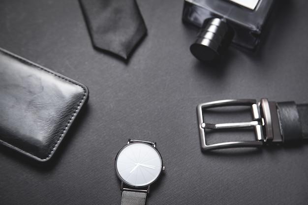 Cravatta, cintura, portafoglio, orologio da polso, profumo su sfondo nero.