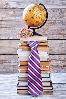 Cravatta, fiori e globo. pila di libri sullo scaffale.