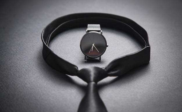 Legare con un orologio da polso sulla superficie nera. accessori da uomo