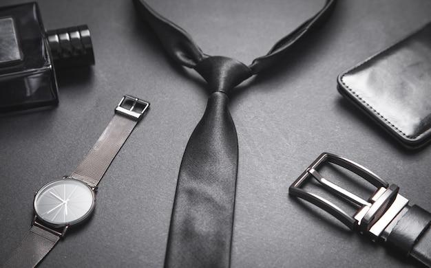 Legare con un orologio da polso e un profumo sulla superficie nera. accessori da uomo