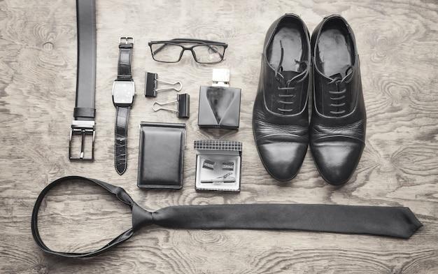 Cravatta, orologio da polso, profumo, cintura, portafoglio, scarpe sullo sfondo nero. accessori da uomo
