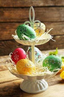 Stand di livello con bellissime uova di pasqua su una superficie di legno, primo piano