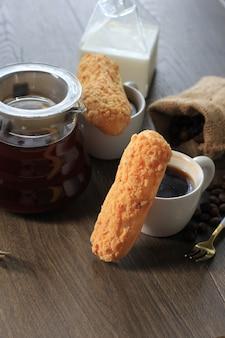 Tiger eclair/craquelin eclair, delizioso dessert francese di pasta choux sopra una griglia nera, appena sfornato, pronto da riempire con crema. copia spazio per testo/pubblicità