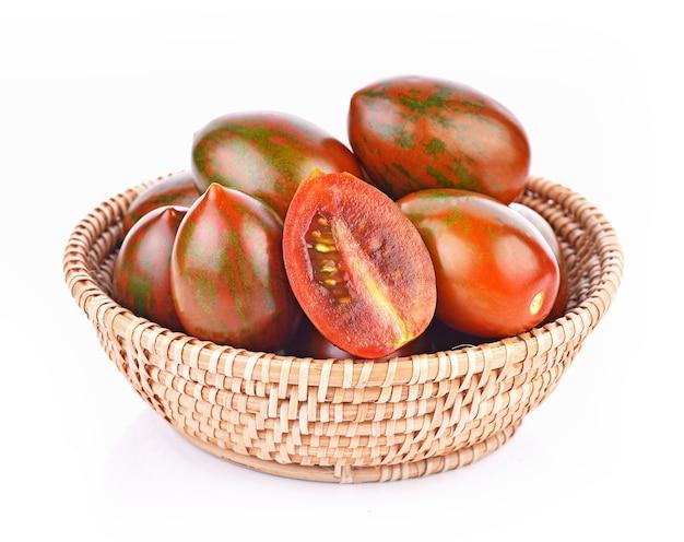 Pomodori tigre in cestino su sfondo bianco Foto Premium
