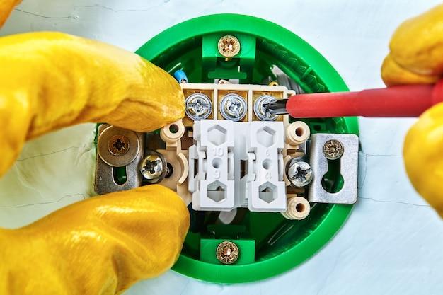 Vite di serraggio nel nuovo interruttore con l'aiuto di uno strumento manuale da parte di un elettricista, impianto elettrico.