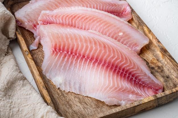 Tilapia tagli di carne di filetto di pesce, su sfondo bianco