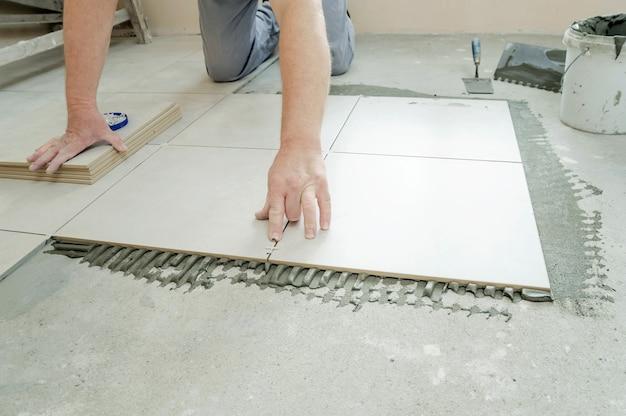 Un piastrellista sta mettendo un distanziatore tra le piastrelle di ceramica.