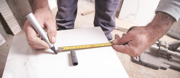 Il piastrellista misura e taglia le piastrelle.