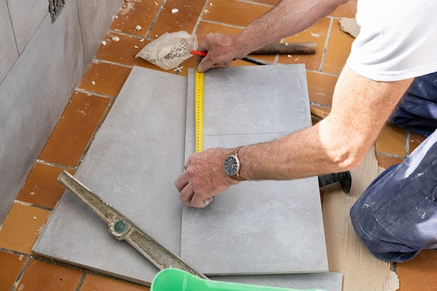 Il piastrellista misura la piastrella prima di tagliarla